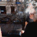 Eine junge Frau lehnt sich aus einen Fenster, es ist ein sonniger Tag, blauer Himmel, im Hintergrund ist ein Schild eines Cafés zu sehen. Die junge Brünette raucht eine Zigarette