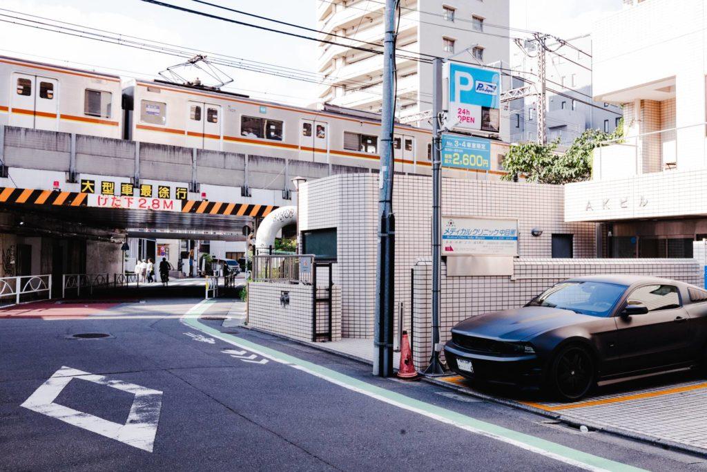 Auf der Aufnahme ist ein Wohnviertel in Tokio zu sehen. Es ist ein heller Sommertag, am rechten Rand steht in einer Hauseinfahrt ein schwarzer Mustang. Mittig verläuft eine Straße unter einer Brücke. Auf der Brücke fährt eine U-Bahn.