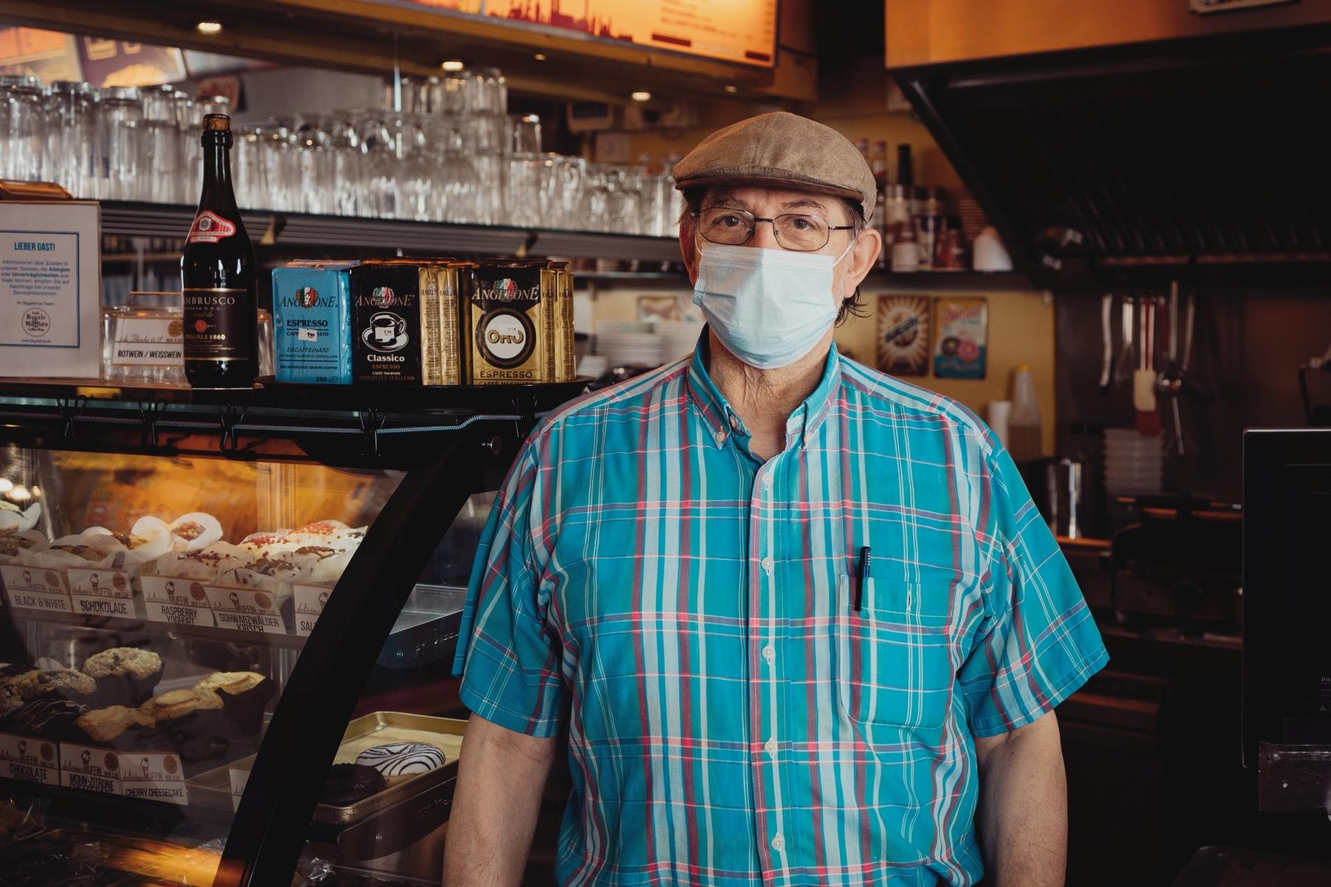 Gastronomie in den roten Zahlen, aufgrund der schwierigen Corona-Krise finden sich Restaurant und Barbetreiber in der Krise. Diese Fotoserie mit Interviews von dem Fotografen Steins Pictures möchte Aufmerksamkeit auf diese prekäre Lage in München erwecken: auf dem Bild ein älterer Gastrobetreiber mit Maske und Mütze vor seiner Theke