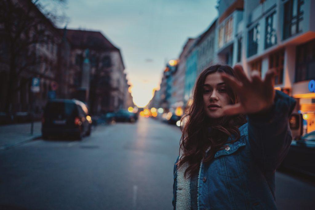 Unscharfe Portraitaufnahme von Eva vor der Münchner Universität, wie sie Ihre Hand richtung Kamera streckt geschoßen von dem Münchner Fototgrafen für Sedcard, Schauspielerfotos und Reportagefotografie Steins Pictures.