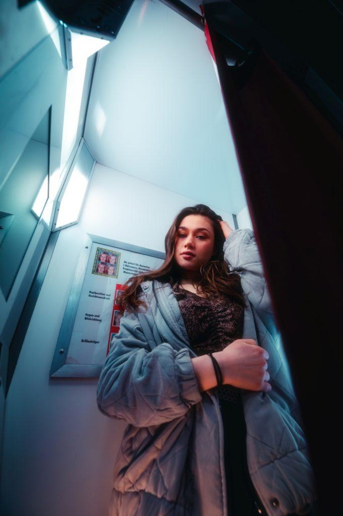 Zu sehen ist ein Porträt aufgenommen in München in Bayern.  Im Porträt Foto ist eine junge Frau zu sehen, zum Teil auch Neon-Lichter, eine U-bahn, Fotoautomat und Rolltreppe. Die Aufnahmen an der Oberfläche wurden in München, nähe Rotkreuzplatz aufgenommen.  Im Hintergrund der Porträts sind eine Schule und ein Krankenhaus zu sehen. Die Bilder sind für eine Portfolio Erweiterung geschossen worden.
