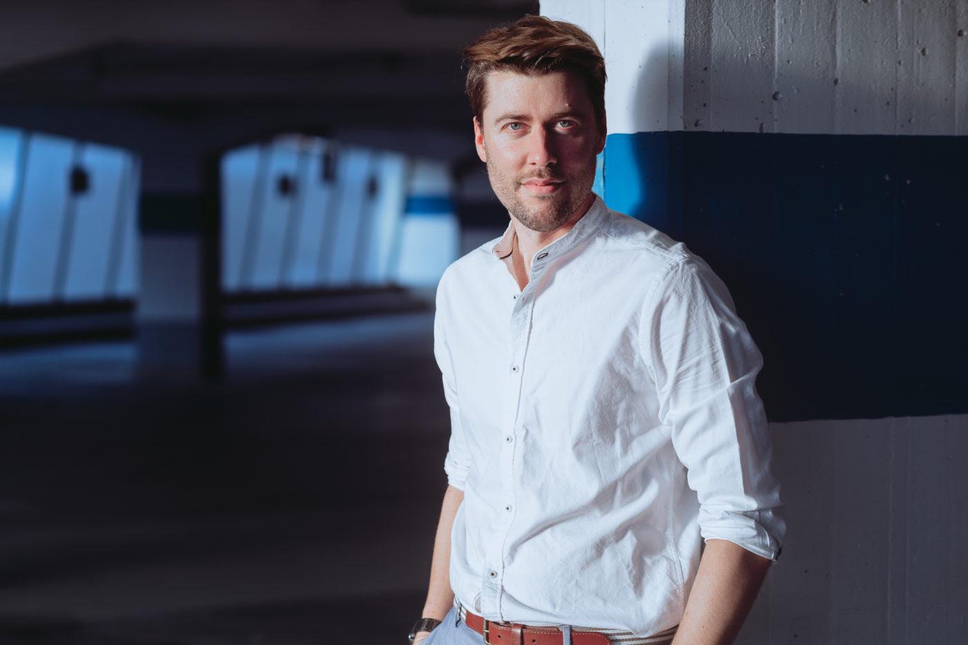 Das etwa 1,80 Meter große, brünette männliche Model Axel posiert in einem Parkhaus in der Abendsonne bei einem Shooting mit dem Münchner Fotograf Daniel Schubert.